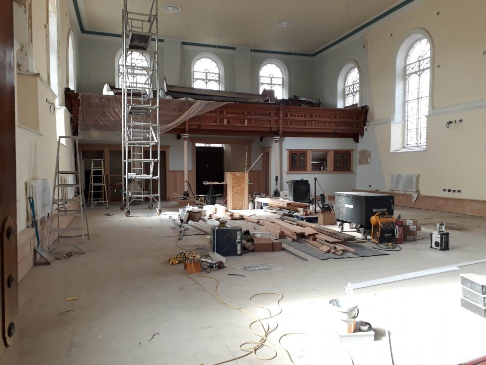 A view of the church from the pulpit end looking towards the entrance showing new floor, new woodwork and the decorating half completed