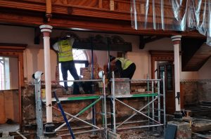 The rear of the church as the new entrance from the vestibule is formed by two builders on scaffolding