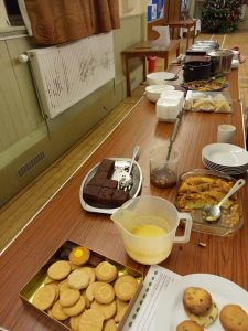 A table with several dessert options ready to be served - custard, chocolate cake, cupcakes