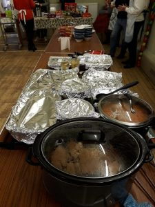 A table with several dishes in pans, covered with foil to keep them warm