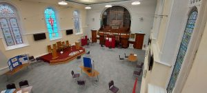 Image of the Sanctuary looking down from the right of balcony, showing the stage with communion table, lectern and chairs and with prayer stations around the rest of the room