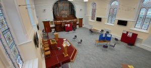 Image of the Sanctuary looking down from the left of the balcony, showing the stage with communion table, lectern and chairs and with prayer stations around the rest of the room
