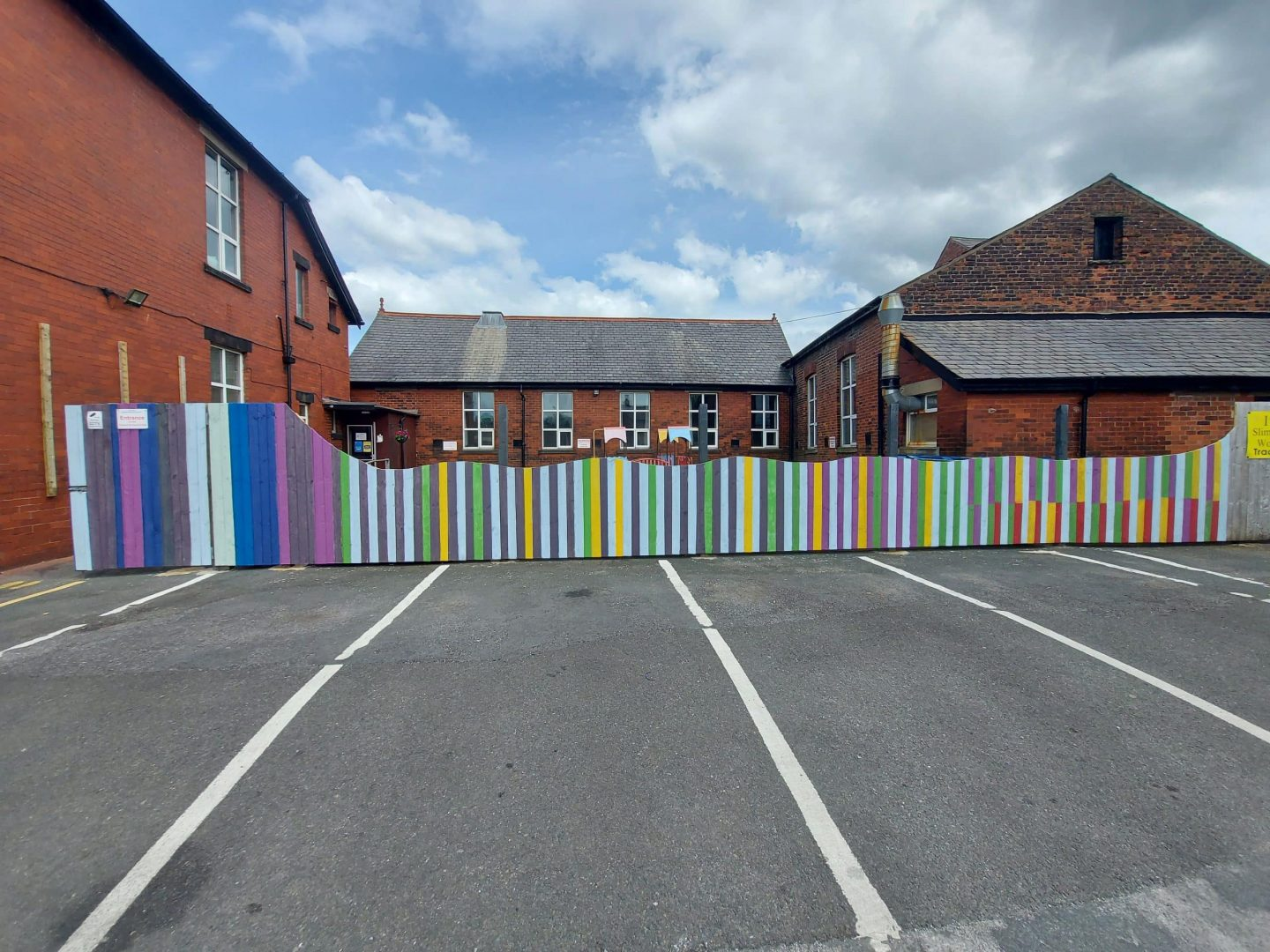 Picture shows courtyard fence at Chorley URC having been painted in bright colours and cut down to around 4 feet high