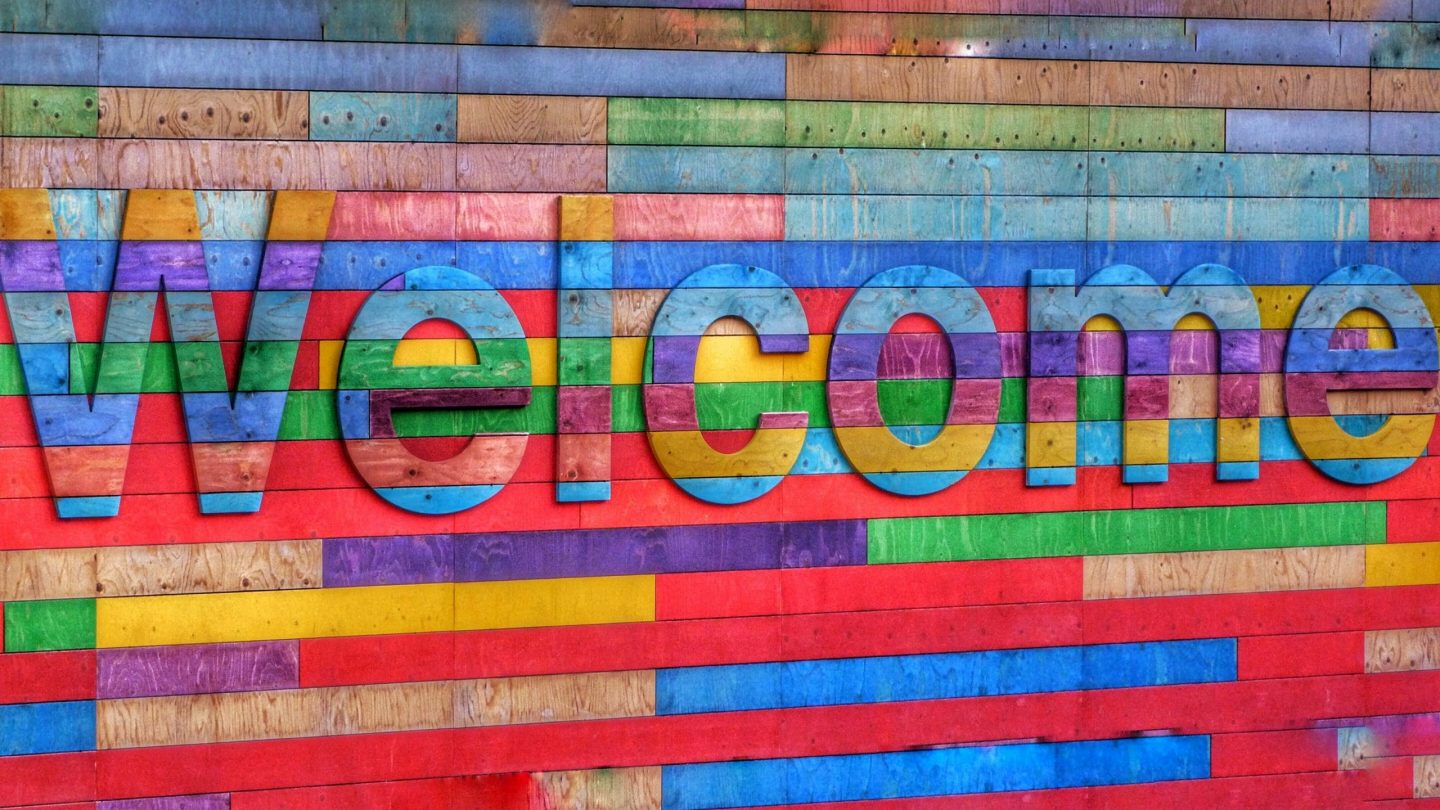 """A brightly coloured sign made of painted wooden slats that says """"welcome"""""""